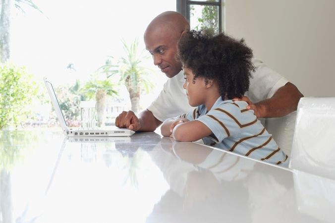 Father And Son Using Laptop At Dining Table